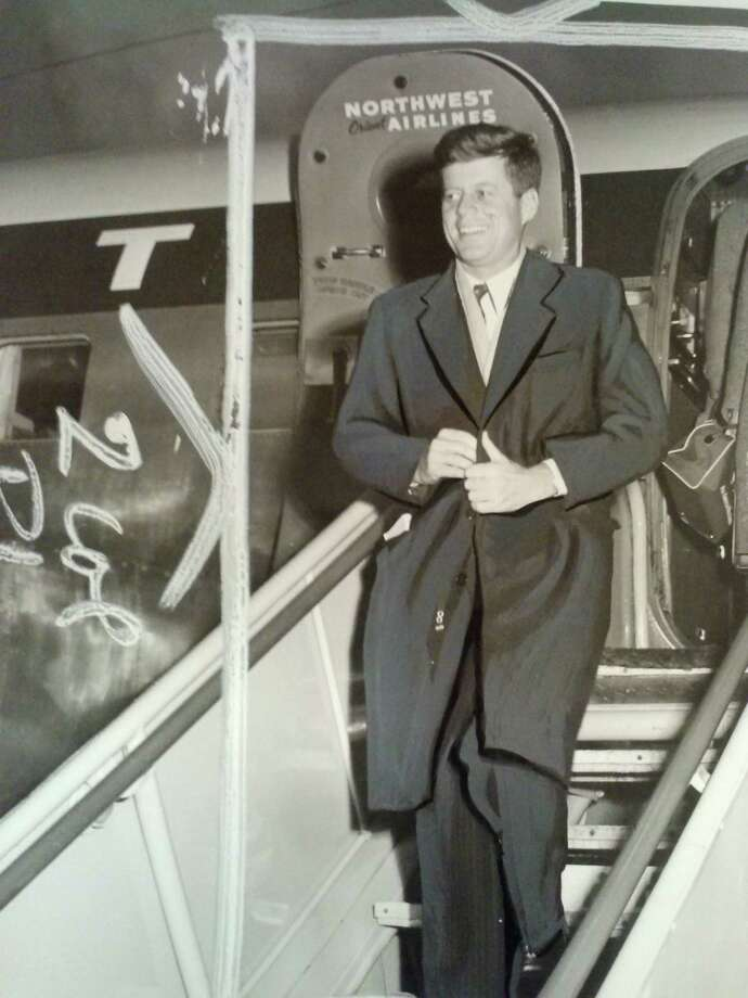 Sen. John F. Kennedy, top contender for the Democratic presidential nomination, buttons coat against weather and grins as he leaves plane at Sea-Tac International Airport morning en route to Alaska November 1959. Photo: Copyright MOHAI, Seattle Post-Intelligencer Collection, 2000.107_print_KennedySeattleVisit
