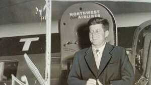 Sen. John F. Kennedy, top contender for the Democratic presidential nomination, buttons coat against weather and grins as he leaves plane at Sea-Tac International Airport morning en route to Alaska. (Date unclear, possibly Nov. 11, 1959)