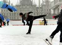 Paul Wylie, 1992 Olympic Silver Medalist, center, glides through the snow on the ice rink on Saturday, Dec. 29, 2012, at the Empire State Plaza in Albany, N.Y. Wylie's visit was sponsored by Starlight Children's Foundation and Hannaford Supermarkets. (Cindy Schultz / Times Union archive)