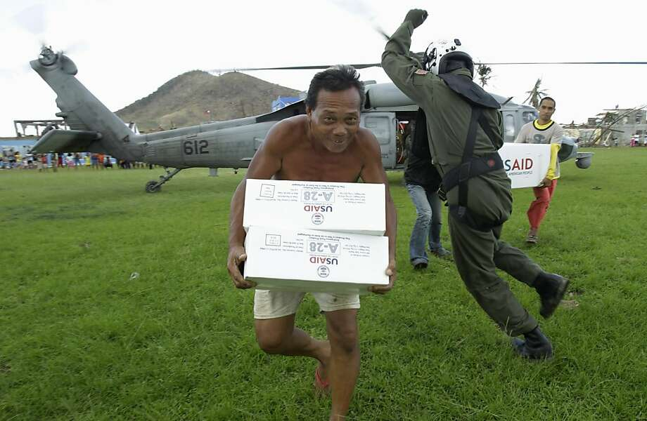 Out of our way! Navy aviation operator Caleb Rausch dodges typhoon victims running with supplies unloaded from a Navy Seahawk 