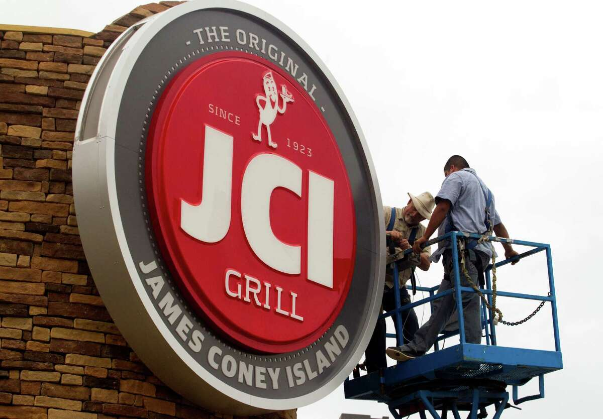 Sign Factory employees Jim Cox, left, and Kenny Tapia install the new JCI Grill sign on the James Coney Island off of Hollister on Wednesday, Nov. 20, 2013, in Houston. The company is gradually changing its name and rebranding itself for a more modern day experience. It will also be expanding its menu.