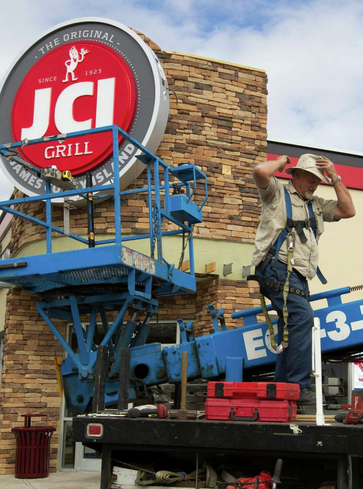 Sign Factory employee Jim Cox comes down off a crane after installing the new JCI Grill sign on the James Coney Island off of Hollister on Wednesday, Nov. 20, 2013, in Houston. The company is gradually changing its name and rebranding itself for a more modern day experience. It will also be expanding its menu.