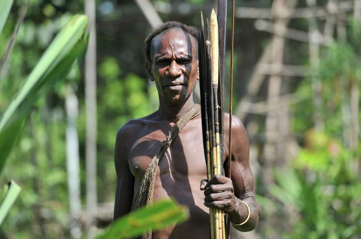 Cos Cob resident Luc Hardy recently traveled to a remote jungle village in West Papua, New Guinea, where encountered members of the Korowai tribe, a primitive group of hunter/gatherers that number about 3,000. Above, a Korowai hunter displays his weapons.