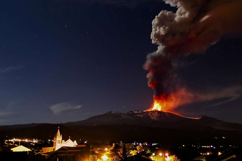 Sicilian heat: Mt. Etna, Europe's most active volcano, spews lava into the night sky as the town of Acireale, Italy, sleeps. Photo: Carmelo Imbesi, Associated Press