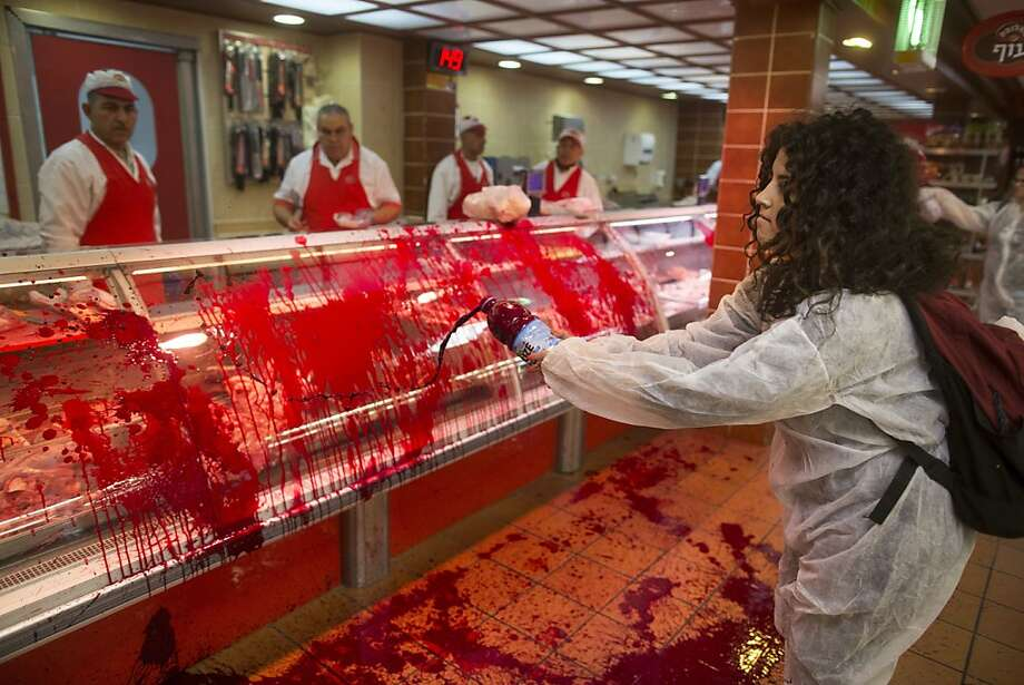 "Store gore galore:An animal-rights activist spills fake blood on a display window at the Soglowek butcher shop in Nahariya, Israel. Police arrested several 269Life activists after they vandalized the store. The name ""269Life"" comes from the brand on a Israeli dairy farm calf that was saved from slaughter. Photo: Uriel Sinai, Getty Images"