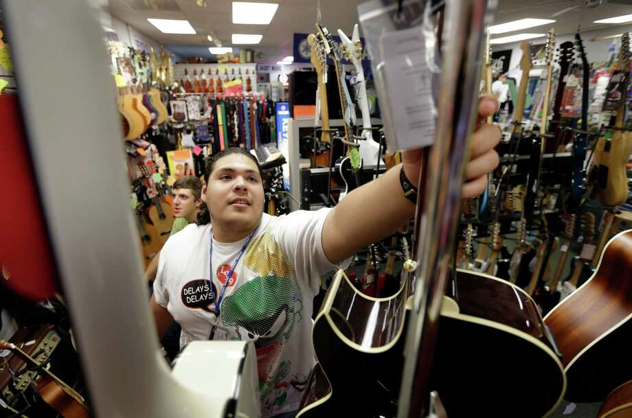 In this Tuesday, Sept. 24, 2013 photo Kevin Sandoval, of Chelsea, Mass., places a guitar on a rack after trying the instrument out at a music store, in Lowell, Mass. The government reports how much U.S. businesses adjusted their stockpiles in September on Wednesday, Nov. 20, 2013. (AP Photo/Steven Senne) ORG XMIT: NYBZ122 Photo: Steven Senne / AP