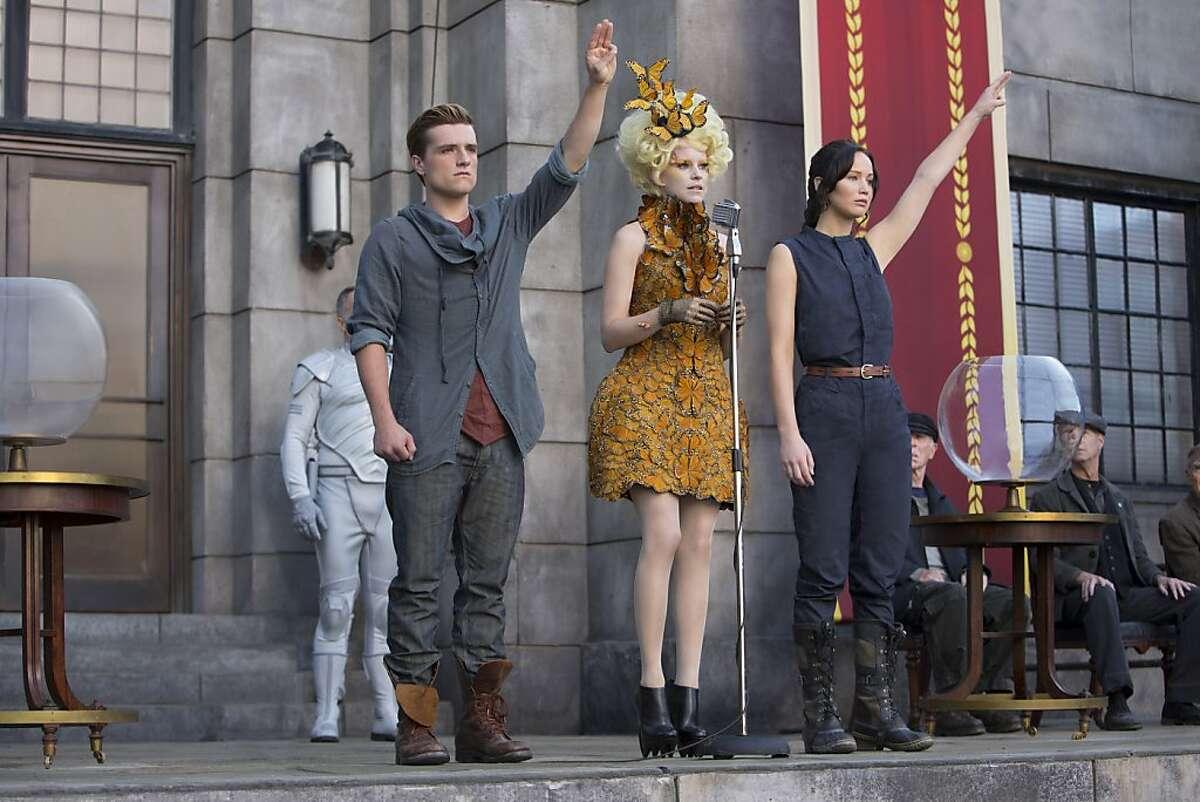 Katniss Everdeen (Jennifer Lawrence, right), Effie Trinket (Elizabeth Banks, center) and Peeta Mellark (Josh Hutcherson, left) in THE HUNGER GAMES: CATCHING FIRE.