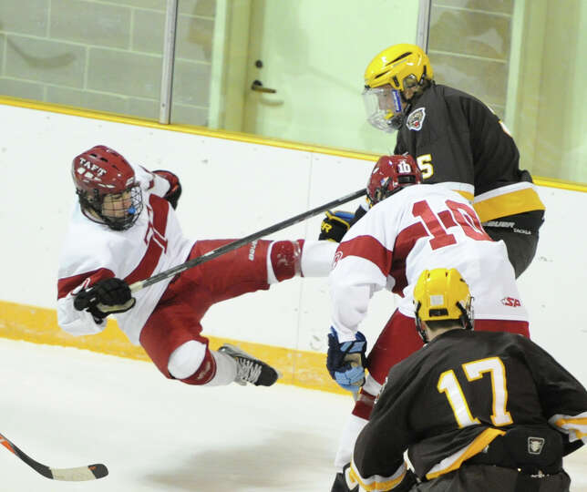 Henry Hobbs (# 5) of Brunswick, at right, checks a Taft player to the ice during the first period of