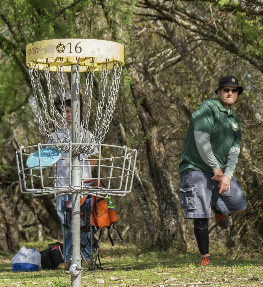 Corey Peschke drops a long putt into the basket while playing disc golf at Live Oak Park.