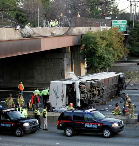 FILE - This March 2, 2007 file photo shows a charter bus carrying the Bluffton University baseball team from Ohio after it plunged off a highway ramp in Atlanta and slammed into the I-75 pavement below. Federal regulators say they will require that new tour buses and buses that carry passengers on scheduled routes between cities be equipped with seat belts. It's a safety measure sought by accident investigators for nearly a half century. The National Highway Traffic Safety Administration said Wednesday that beginning in November 2016 all new motorcoaches and other large buses must be equipped by manufacturers with three-point lap-shoulder belts.  (AP Photo/Gene Blythe, File) Photo: Gene Blythe, STF / AP