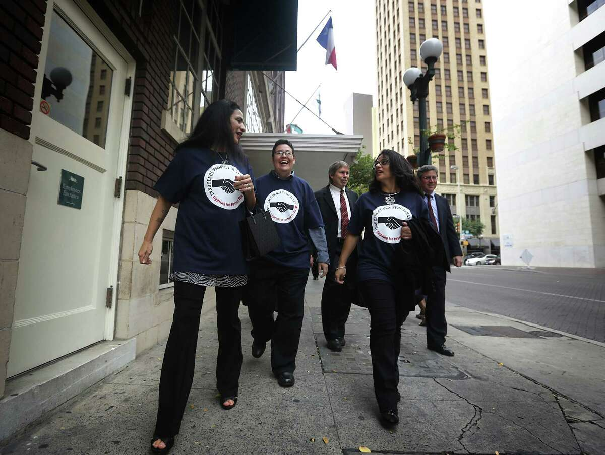 Cassandra Rivera, left, Kristie Mayhugh, center, and Elizabeth Ramirez, right, walk freely in downtown San Antonio with two of their lawyers after holding a press conference with their lawyers in the Tower Life Building. Wednesday, Nov. 20, 2013. Anna Vasquez, the fourth of the SA 4, is walking behind them.