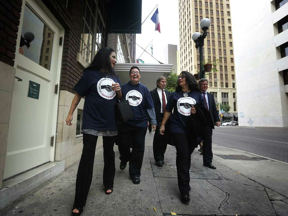 Cassandra Rivera, left, Kristie Mayhugh, center, and Elizabeth Ramirez, right, walk freely in downtown San Antonio with two of their lawyers after holding a press conference with their lawyers in the Tower Life Building. Wednesday, Nov. 20, 2013.  Anna Vasquez, the fourth of the SA 4, is walking behind them. Photo: BOB OWEN, San Antonio Express-News / © 2012 San Antonio Express-News