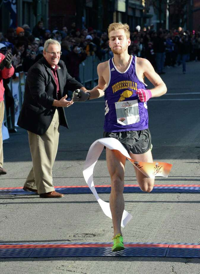 Troy Mayor Lou Rosamilia holds the finish line tape as 5K race winner Mackey Lloyd of Voorheesville crosses the finish line in the 65th running of the Troy Turkey Trot in Troy, N.Y. Nov 22, 2012.     (Skip Dickstein/Times Union) Photo: Skip Dickstein / 00020181A