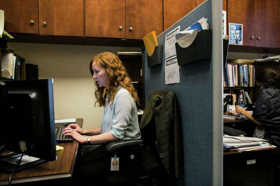 Jacqueline Thomas, a legislative correspondent for Rep. Debbie Wasserman Schultz (D-Fla.) who recently purchased a health insurance plan through a local Washington exchange, works at her office in Washington, Nov. 18, 2013. While millions of Americans have been frustrated trying to get insurance through the federal exchange, lawmakers and their aides have all sorts of concierge-type assistance to help them sort through their options and enroll. (T.J. Kirkpatrick/The New York Times) Photo: TJ KIRKPATRICK, STR / NYTNS