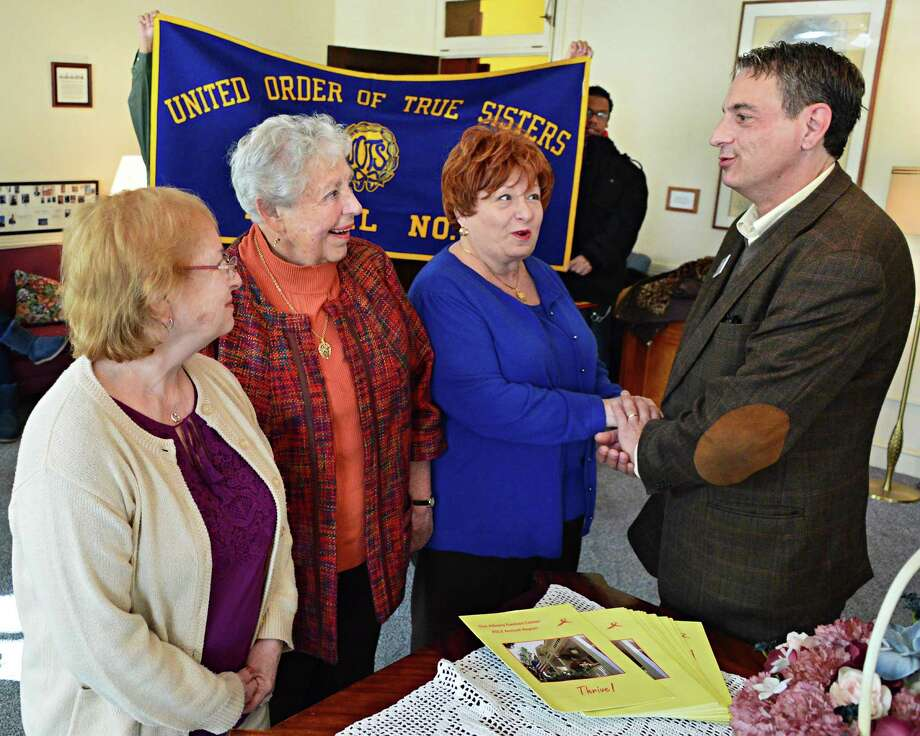 Past presidents of the United Order of True Sisters, from left, Harriet Wicks, Sally Tillman and Anna Bender with Albany Damien Center director Perry Junjulas, at right, at the First Lutheran Church, the Damien Center's temporary headquarters Thursday November 14, 2013, in Albany, NY. The United Order of True Sisters is closing its doors after 175 years and will provide the Albany Damien Center with the balance of its funds, totaling $10,000.  (John Carl D'Annibale / Times Union) Photo: John Carl D'Annibale / 00024583A