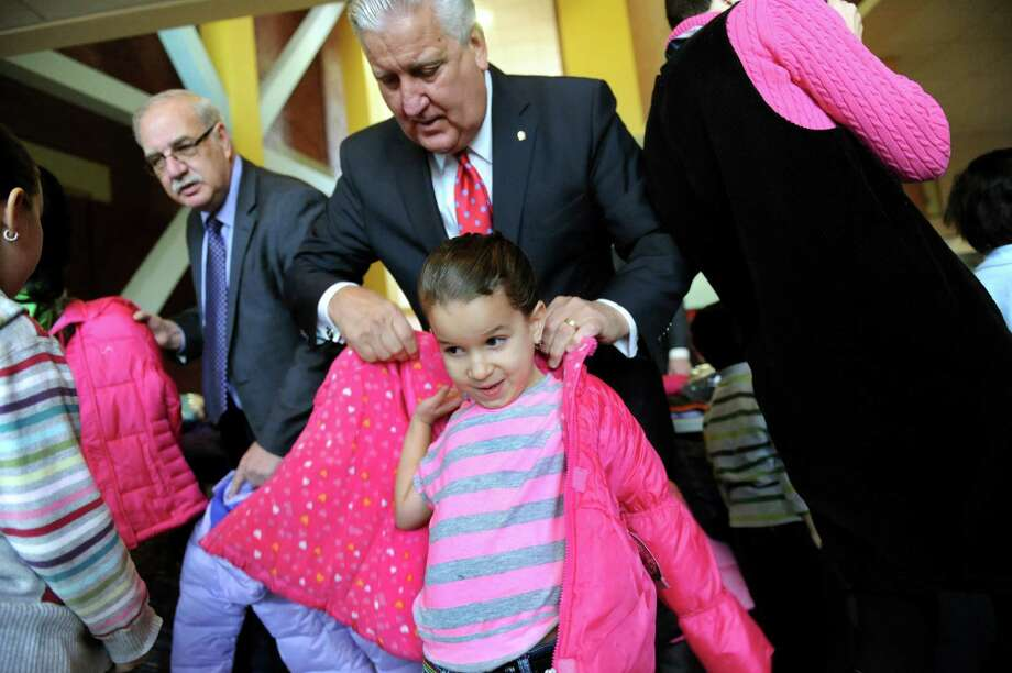 Kimberly Montes, 5, center, gets help from Mayor Jerry Jennings as she tries on a new coat during a news conference on Wednesday, Nov. 20, 2013, at Schuyler Achievement Academy in Albany, N.Y. The mayor and event sponsors presented donated outerwear as part of the 2013 Mayor's Cash for Coats Drive, a National Make A Difference Day initiative. (Cindy Schultz / Times Union) Photo: Cindy Schultz / 00024721A