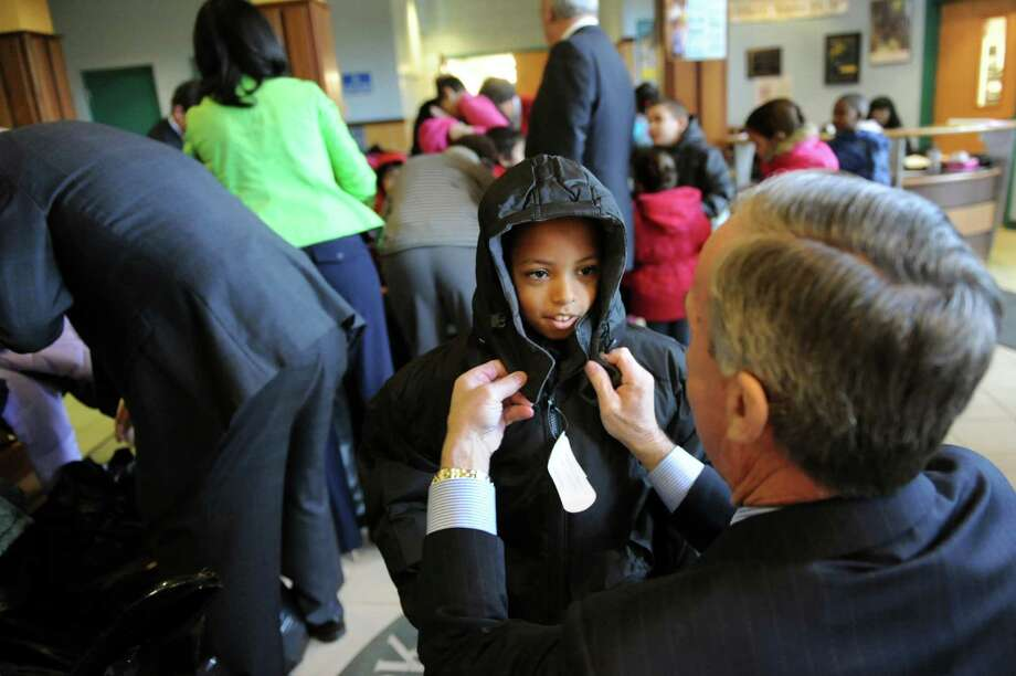 Jose Botex, 8, center, gets help from Chris Ciceri, CEO of the Albany Devils, as he tries on a new coat during a news conference on Wednesday, Nov. 20, 2013, at Schuyler Achievement Academy in Albany, N.Y. Mayor Jerry Jennings (not pictured) and event sponsors presented donated outerwear as part of the 2013 Mayor's Cash for Coats Drive, a National Make A Difference Day initiative. (Cindy Schultz / Times Union) Photo: Cindy Schultz / 00024721A