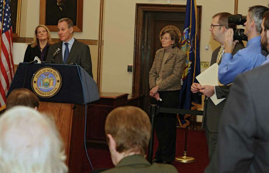 Attorney General Eric Schneiderman discusses the 13 billion dollar settlement with JP Morgan on Wednesday, Nov. 20, 2013 in Albany, N.Y. Kirsten Keefe of the Empire Justice Center, left, and Susan Cotner of the Capital Region's Affordable Housing Partnership, third from left, listen behind him. (Lori Van Buren / Times Union) Photo: Lori Van Buren / 00024730A