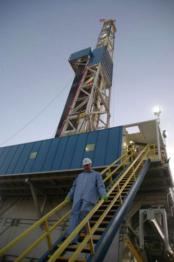 Interior Secretary Ken Salazar climbs stairs down from a rig drilling an oil well for Newfield Exploration Co. in North Dakota. The company expects to drill two wells at the site tapping the Bakken formation and eventually produce 3,000 barrels per day of oil. Jennifer A. Dlouhy/Houston Chronicle Photo: Jennifer A. Dlouhy / Houston Chronicle