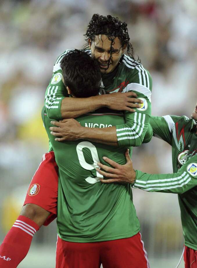 Mexico's Carlos Peña (top) embraces Aldo de Nigris after scoring against New Zealand in a World Cup qualifier. Photo: Ross Setford / Associated Press