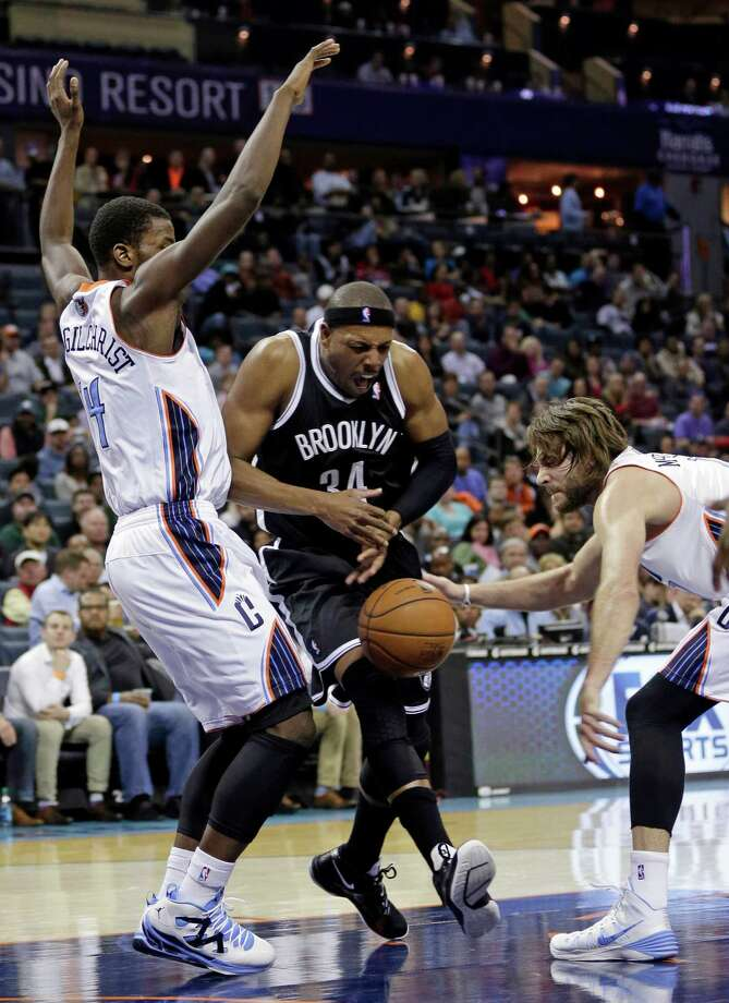 Brooklyn Nets' Paul Pierce, center, loses the ball as he drives between Charlotte Bobcats' Michael Kidd-Gilchrist, left, and Josh McRoberts, right, during the second half of an NBA basketball game in Charlotte, N.C., Wednesday, Nov. 20, 2013. The Bobcats won 95-91. (AP Photo/Chuck Burton) ORG XMIT: NCCB115 Photo: Chuck Burton / AP