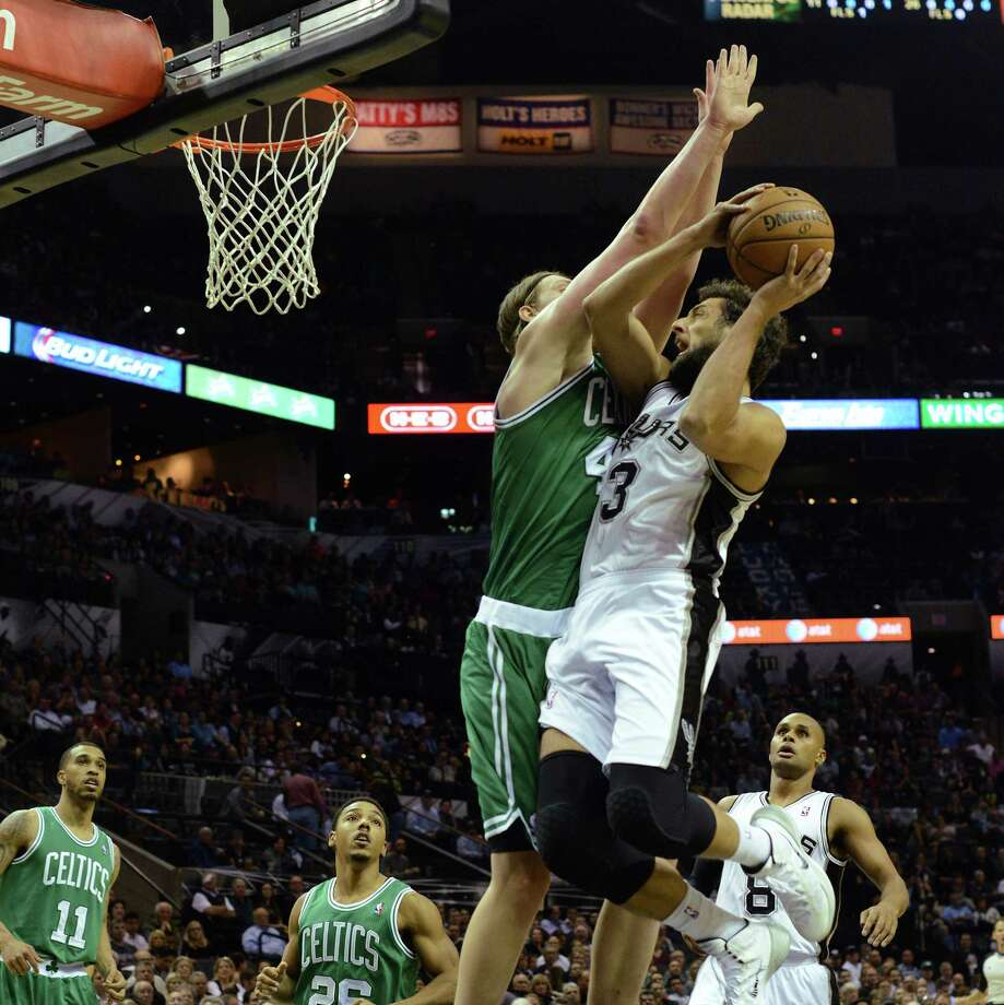 Maro Belinelli of the San Antonio Spurs drives as Kelly Olynyk of the Boston Celtics defends during NBA action at the AT&T Center on Wednesday, November 20, 2013. Photo: Billy Calzada, Staff / San Antonio Express-News