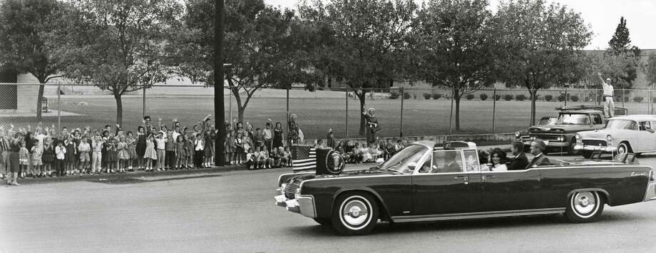 Stanley McClellan (right background) waves from his vantage point on the back of his Southwestern Bell truck as he and schoolchildren from Cambridge School watch President John F. Kennedy's motorcade go down Broadway on Nov. 21, 1963. Photo: Jim Berg / Courtesy MatsonCreative.com
