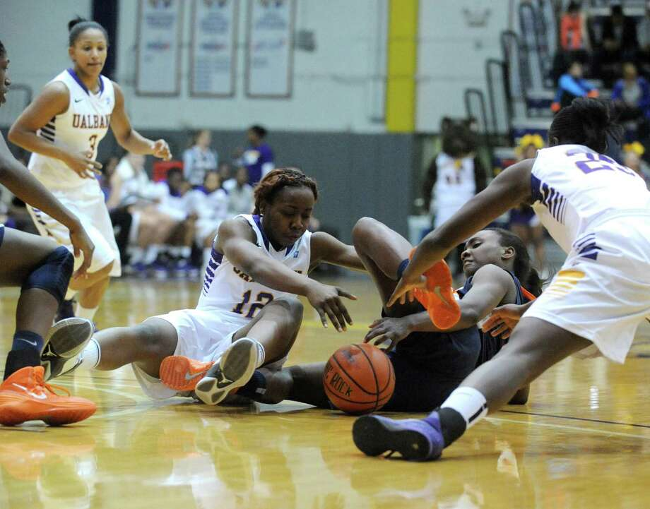 UAlbany's Imani Tate and Cal-State Fullerton's Alex Thomas battle for a loose ball during their womens college basketball game on Wednesday Nov. 20, 2013 in Albany, N.Y. (Michael P. Farrell/Times Union) Photo: Michael P. Farrell / 00024709A