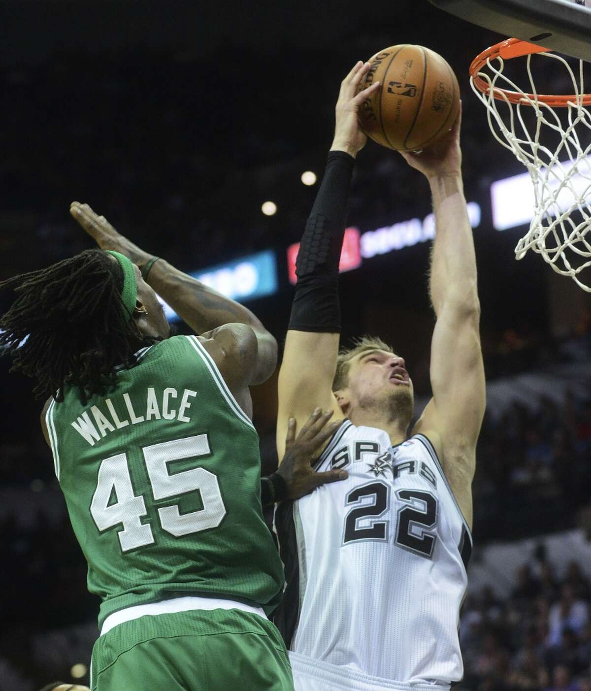 Tiago Splitter of the San Antonio Spurs dunks the ball against Gerald Wallace of the Boston Celtics during second-half NBA action at the AT&T Center on Wednesday, November 20, 2013. The Spurs won, 104-93.