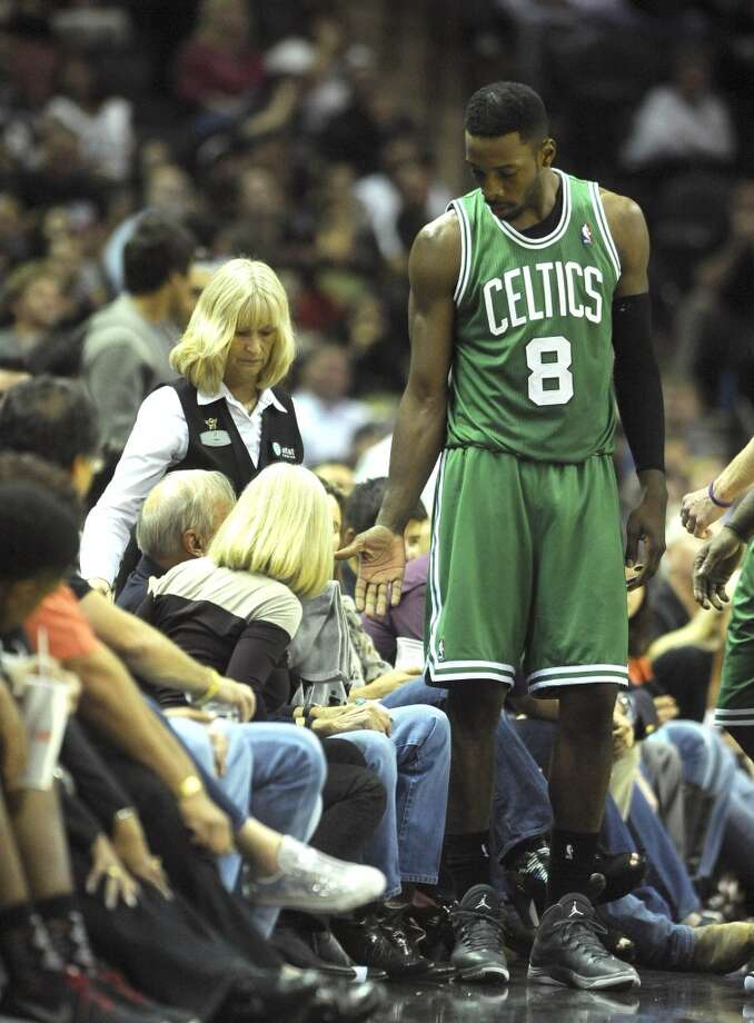 Jeff Green of the Boston Celtics extends a hand to a fan who was hit by an errant ball during second-half NBA action at the AT&T Center on Wednesday, November 20, 2013. The Spurs won, 104-93. Photo: San Antonio Express-News