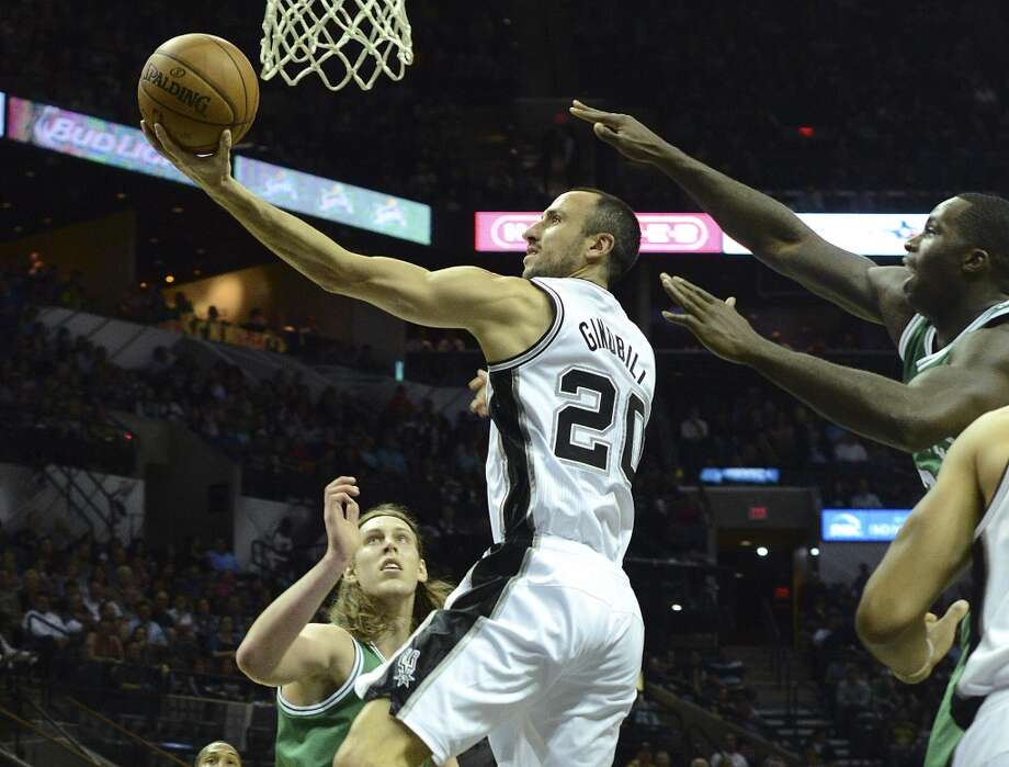 Manu Ginobili of the San Antonio Spurs lays the ball up against Kelly Olynyk of the Boston Celtics during NBA action at the AT&T Center on Wednesday, November 20, 2013. Photo: San Antonio Express-News