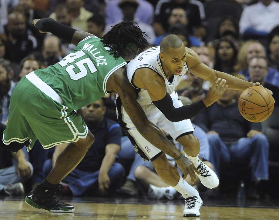 Patty Mills of the San Antonio Spurs takes the ball from Gerald Wallace of the Boston Celtics during NBA action at the AT&T Center on Wednesday, November 20, 2013. Photo: San Antonio Express-News
