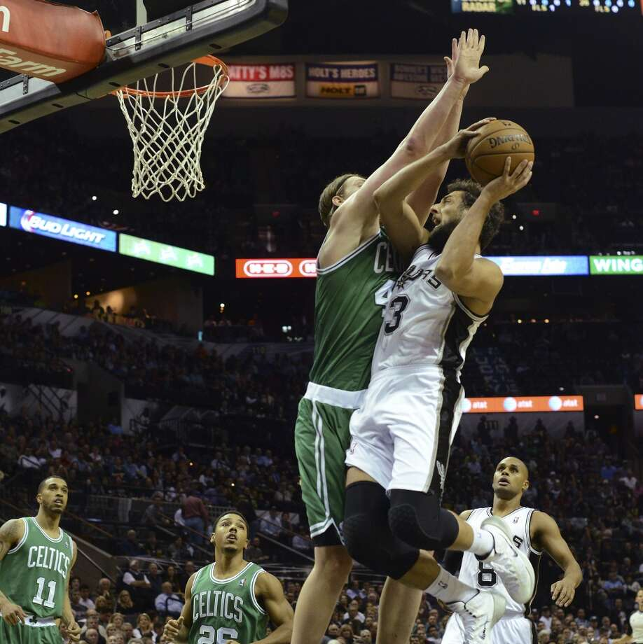Maro Belinelli of the San Antonio Spurs drives as Kelly Olynyk of the Boston Celtics defends during NBA action at the AT&T Center on Wednesday, November 20, 2013. Photo: San Antonio Express-News