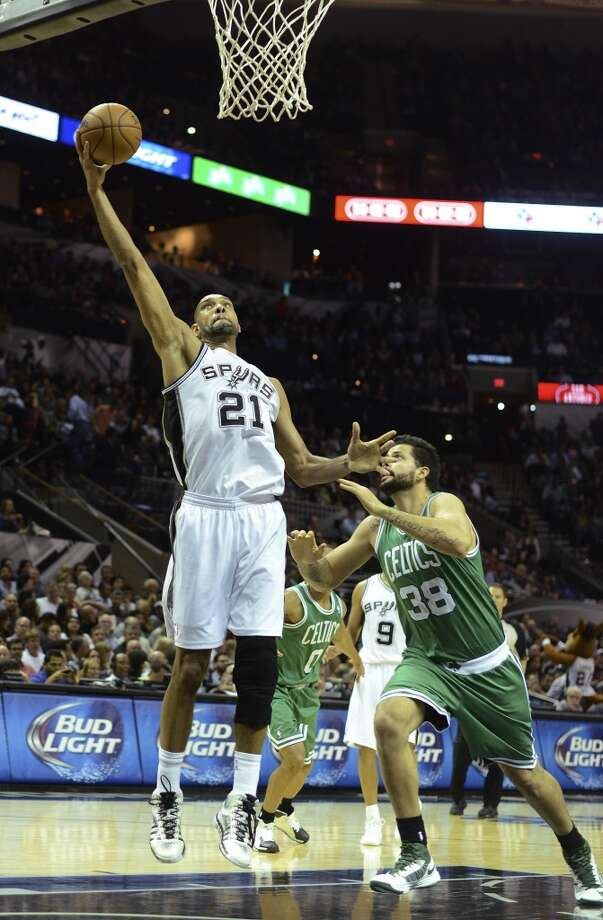 Tim Duncan of the San Antonio Spurs shoots as Vitor Faverani of the Boston Celtics rushes to defend during NBA action at the AT&T Center on Wednesday, November 20, 2013. Photo: San Antonio Express-News