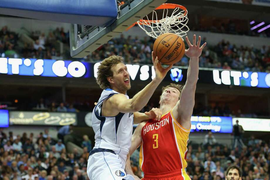 Omer Asik, seeing action in the first quarter Wednesday night, cuts off a drive by Dirk Nowitzki and forces the Mavericks forward to pass. Photo: Ronald Martinez, Staff / 2013 Getty Images