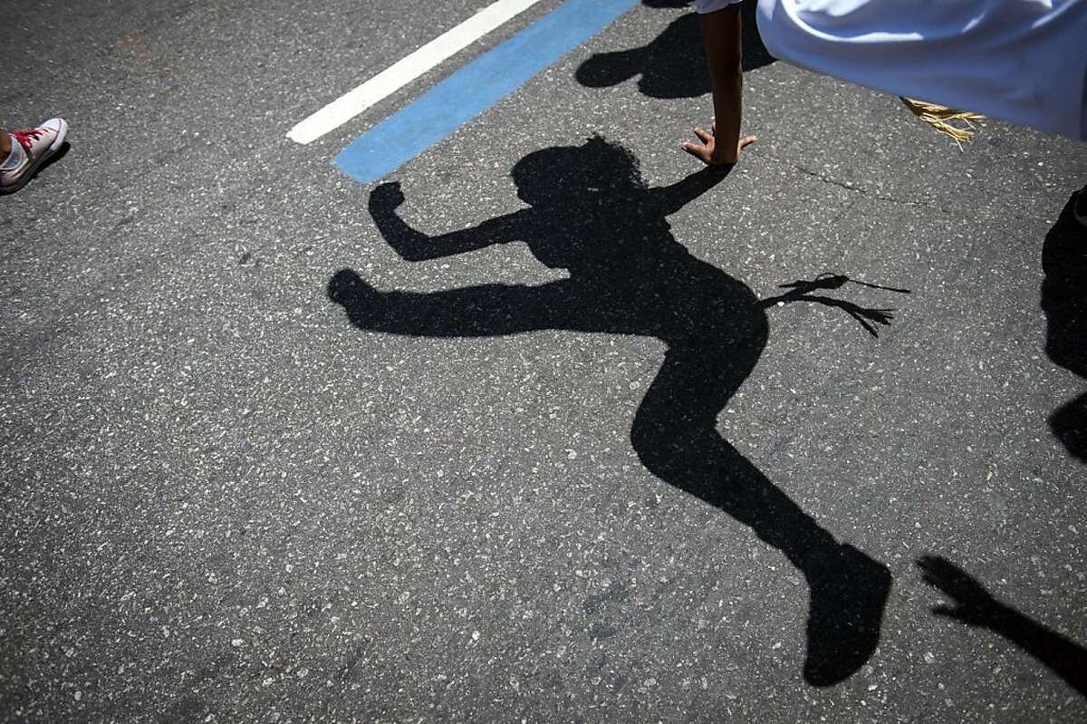 View of the shadow of a woman dancing Capoeira, a Brazilian martial art with elements of dance and acrobatics, during the Black Awareness Day on November 20, 2013, in Rio de Janeiro, Brazil. The Black Awareness Day commemorates the anniversary of the death in 1695 of Zumbi, the leader of the