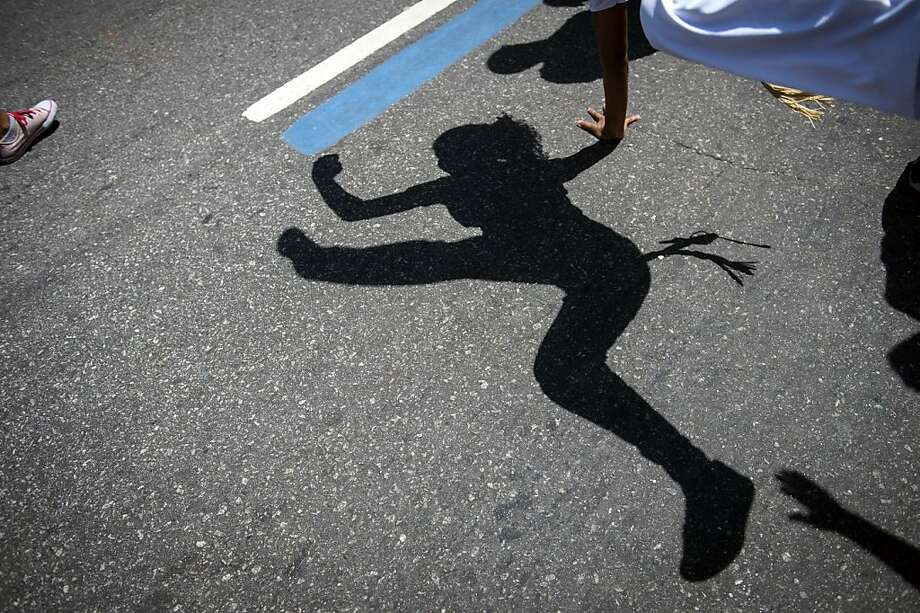 "View of the shadow of a woman dancing Capoeira, a Brazilian martial art with elements of dance and acrobatics, during the Black Awareness Day on November 20, 2013, in Rio de Janeiro, Brazil. The Black Awareness Day commemorates the anniversary of the death in 1695 of Zumbi, the leader of the ""Quilombo dos Palmares"", a fugitive community of escaped slaves of the colonial times.  TOPSHOTS/AFP PHOTO / YASUYOSHI CHIBAYASUYOSHI CHIBA/AFP/Getty Images Photo: Yasuyoshi Chiba, AFP/Getty Images"