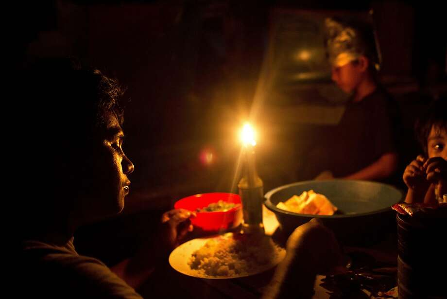 A Typhoon Haiyan survivor and his sons eat dinner by candlelight inside a destroyed and abandoned vegetable market now used as a shelter in Tacloban, Philippines Wednesday, Nov. 20, 2013. Hundreds of thousands of people were displaced by Typhoon Haiyan, which tore across several islands in the eastern Philippines on Nov. 8. (AP Photo/David Guttenfelder) Photo: David Guttenfelder, Associated Press