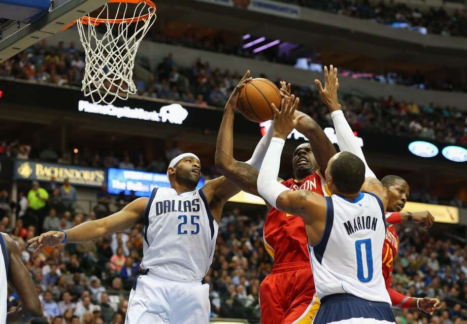 Terrence Jones #6 of the Rockets grabs a rebound against Vince Carter #25 and Shawn Marion. Photo: Ronald Martinez, Getty Images