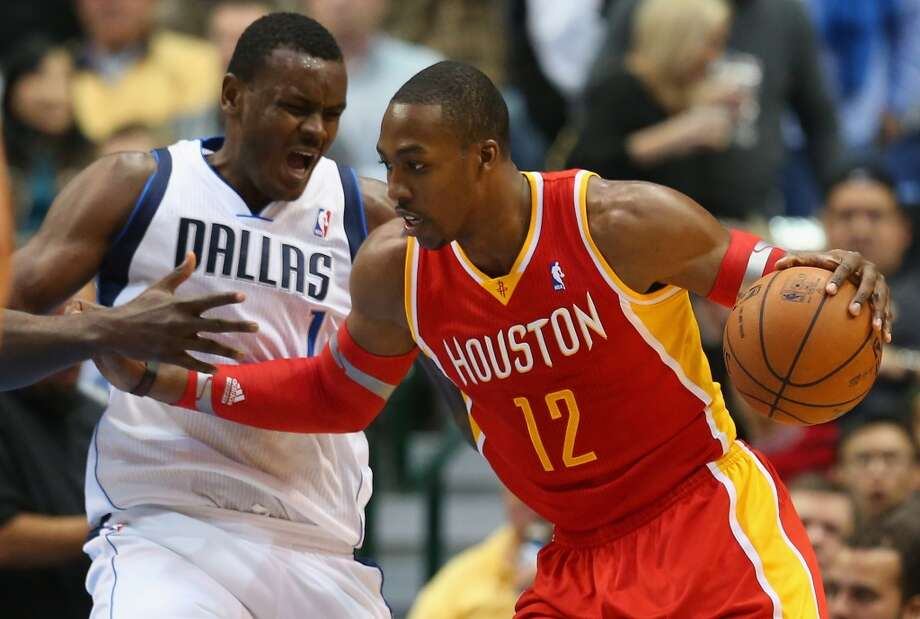 Dwight Howard #12 of the Rockets dribbles the ball against Samuel Dalembert #1. Photo: Ronald Martinez, Getty Images