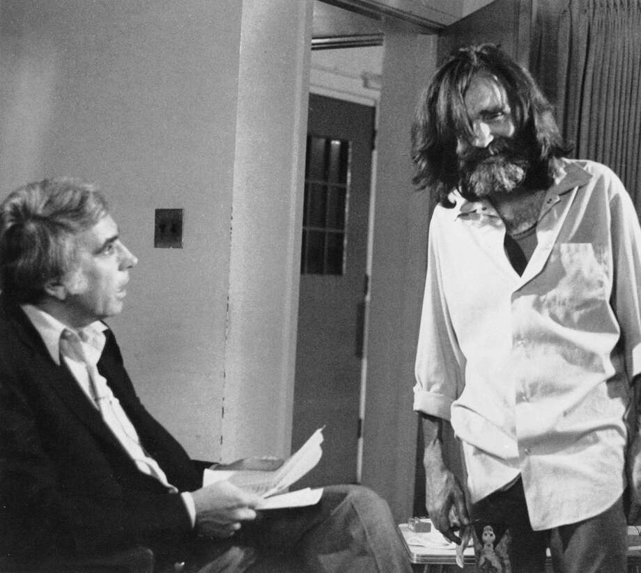 This June 1981 file photo shows talk show host Tom Snyder, left, getting ready to interview convicted murderer Charles Manson at the California Medical Facility in Vaccaville. Photo: AP