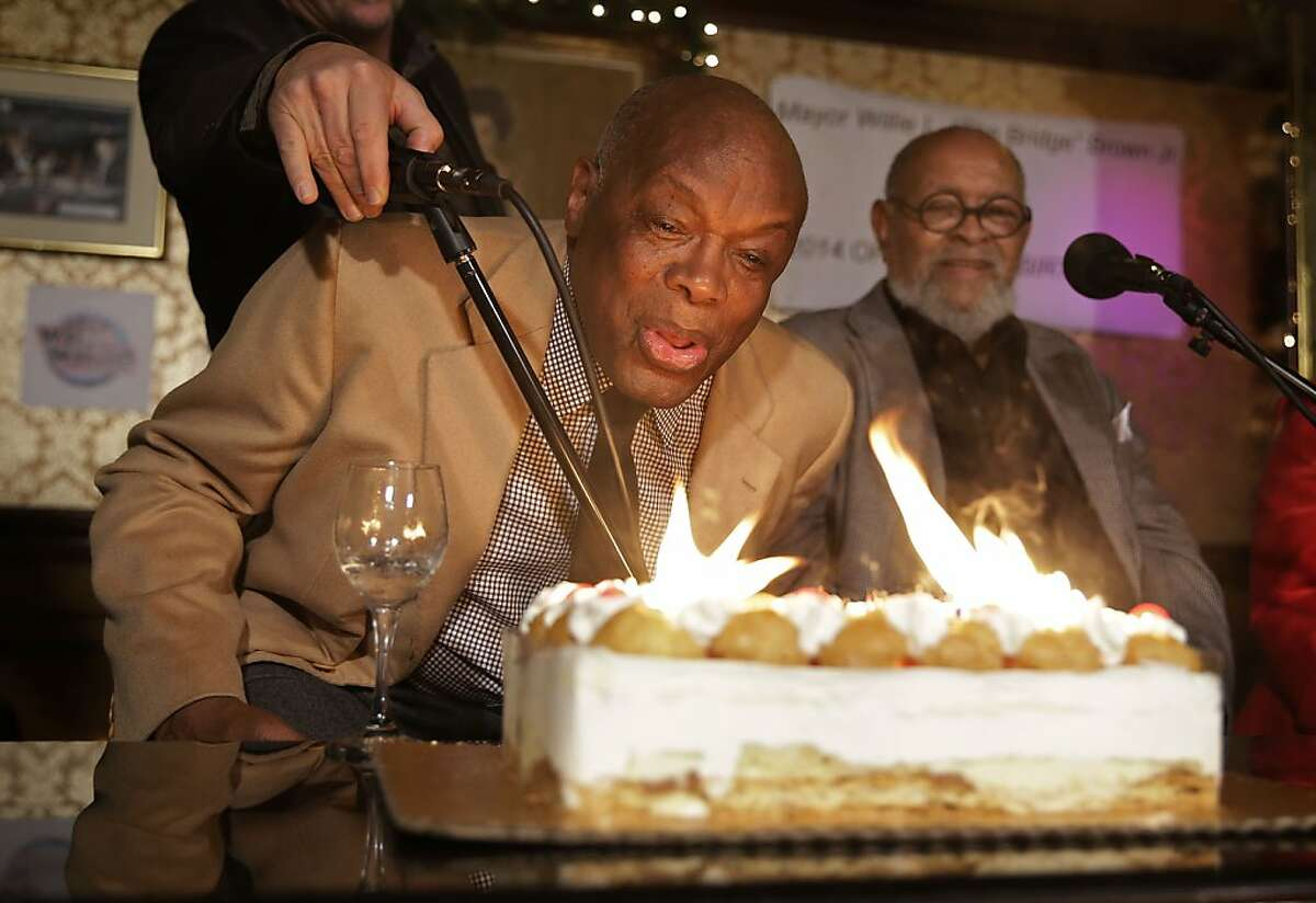 Former San Francisco Mayor and state Assembly Speaker Willie Brown tries to blow out candles on a birthday cake for his upcoming 80th birthday as Rev. Cecil Williams, right, of Glide Memorial Church looks on at the Gold Dust Lounge Wednesday, Nov. 20, 2013, in San Francisco. The lounge, which reopened earlier this year on Fisherman's Wharf after moving from Union Square, is also celebrating its 80th birthday. Brown was at the lounge doing his radio show and was surprised with the cake. (AP Photo/Eric Risberg)
