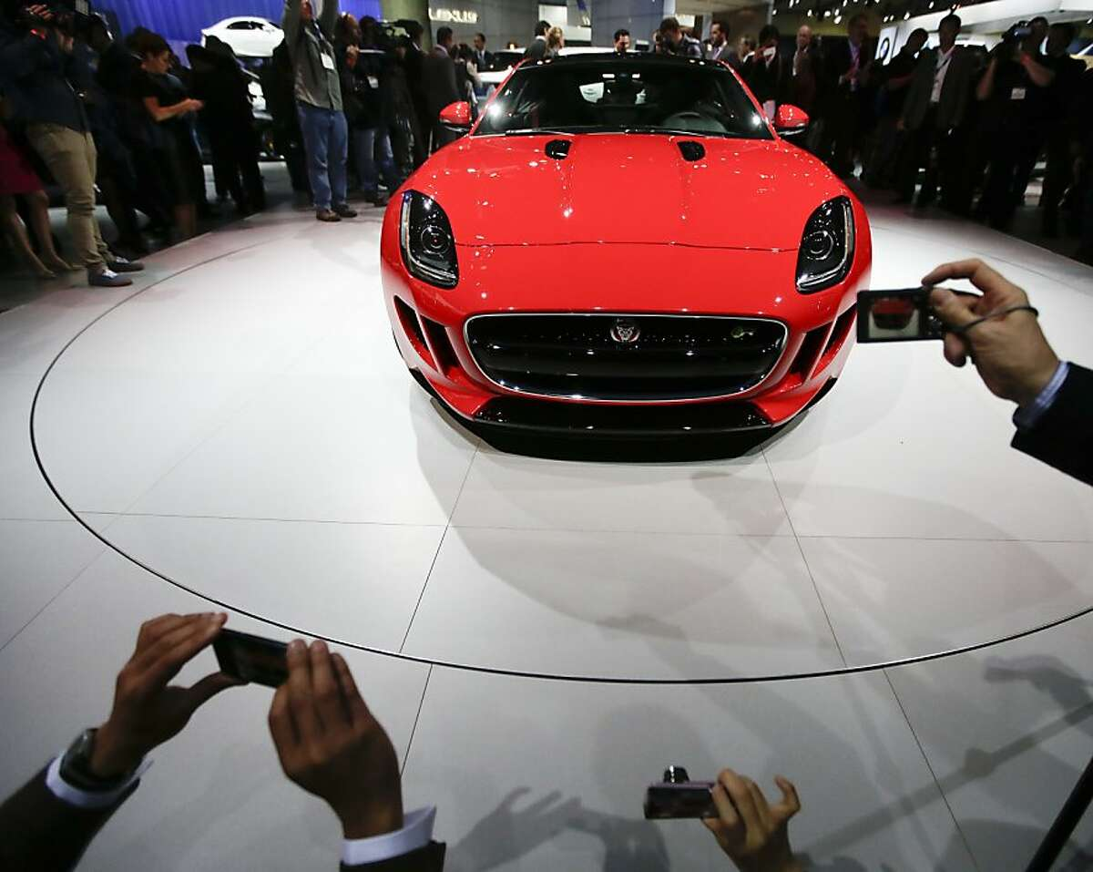 Attendees take pictures after the Jaguar F-Type Coupe was introduced at the Los Angeles Auto Show in Los Angeles, Wednesday, Nov. 20, 2013. (AP Photo/Chris Carlson)