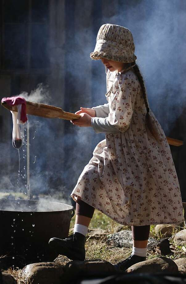 Who wants boiled socks? Nine-year-old Stella Murray removes steaming socks from a cauldron of hot water during a frontier laundry 
