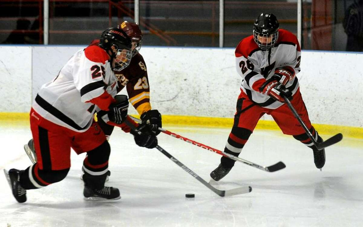Fairfield's #25 Henry Simonds, left, and teammate #26 Tom Kryspin, right, try to keep the puck away from St. Joseph's #23 Kevin Robitaille, during game action at the Wonderland of Ice rink in Bridgeport, Conn. on Saturday Jan. 30, 2010.