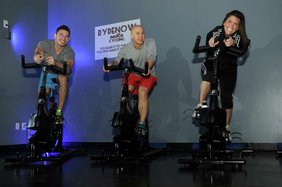 Josh Graye, from left, and Jared Bleiler, both of Cypress and co-owners of Rydenow Indoor Cycling in The Woodlands, take a ride on The Realryder with their class instructor, Robin Wallace, of The Woodlands. Photo: Jerry Baker, Freelance