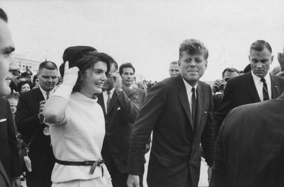 """November 21, 1963: President Kennedy arrives in San Antonio to begin his visit to Texas. """"I shook the hand of President John F. Kennedy at the Rice Hotel the night before his assassination. My mother was an officer in her L.U.L.A.C. club, and she and I attended a banquet being held there on 11/21/63. We drove in from Port Arthur to see the President and First Lady. I was a 19 year old, college freshman. When the President walked into the room, I ran up to the dais. He spoke and then introduced his wife. Mrs. Kennedy spoke to us in Spanish in her soft voice. When they were about to leave, I yelled out, """"Mr. President, Mr. President,"""" and I raised my hand up to him, hoping to shake his hand. He walked over to me, bent down and took my hand in his and gave me a big smile. I remember looking up into his blue eyes and seeing his reddish, brown hair. His hand felt so soft. On the way home, my mother remembers that I was on cloud nine. The next day, when I was entering my biology class, a friend walked over to me and told me that the president had been shot. I was so angry with this classmate. It couldn't be true. My mother and I were in shock for the next several days. We had just seen this wonderful man, so alive and vibrant and with so much promise."""" Ellen Guajardo Talus of Houston"""