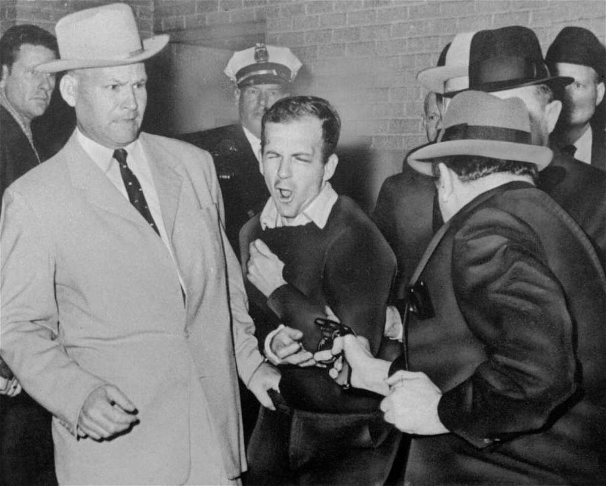 Lee Harvey Oswald, accused assassin of President John F. Kennedy, reacts as Dallas night club owner Jack Ruby, foreground, shoots at him from point blank range in a corridor of Dallas police headquarters, in this Nov. 24, 1963 file photo. At left is Jim A. Leavelle.