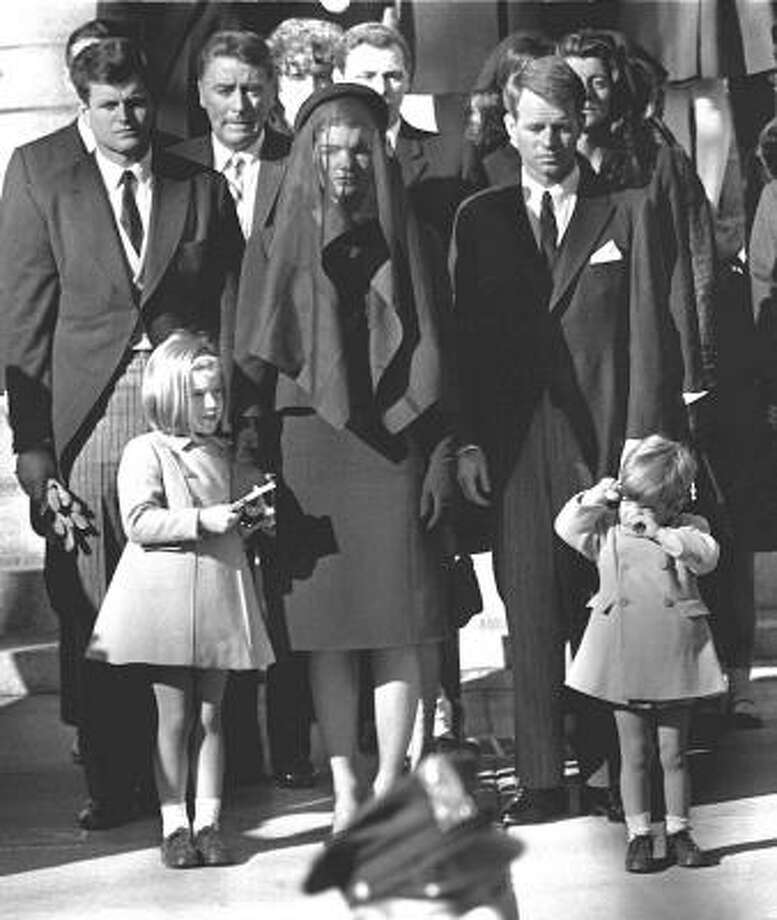 "November 26, 1963: President Kennedy is laid to rest.""I was moving to Washington, D.C. That night, we found an eerie, surreal scene — a deserted capital city and its lighted monuments, but almost no people or cars on the streets except police. Everyone was at home, glued to their TVs. The next night was a completely different scene, however. My sister and I went to the Capitol to see the president lying in state, and I will never forget the throngs of people still arriving when we left at 1 a.m. The following Thursday morning, Thanksgiving, my mother, sister and I decided to go to Arlington Cemetery to see JFK's burial site. While we were walking up the hill, Mrs. Kennedy arrived unannounced. We stood aside respectfully as she walked by. It was a moving, unforgettable moment.""John Paul Jones of Kingwood Photo: -, AFP/Getty Images"