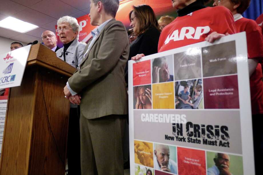 Jeri Cayan, left at podium, of Clifton Park talks about providing care for her husband during a  press conference held by AARP at the Legislative Office Building on Thursday, Nov. 21, 2013 in Albany, NY.  The press event was held for AARP to release a legislative blueprint for improving New YorkOs approach to supporting the 4.1 million unpaid family caregivers.   (Paul Buckowski / Times Union) Photo: Paul Buckowski / 00024739A